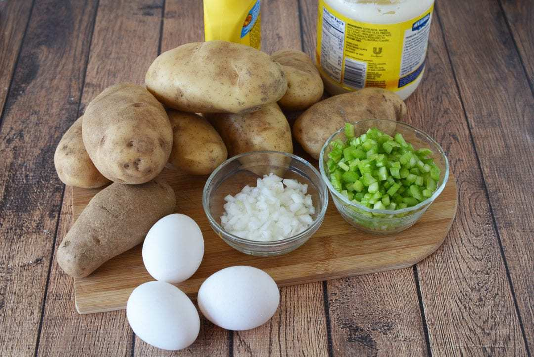 ingredients for potato salad, potatoes, eggs, celery, onion, mayonnaise, and mustard