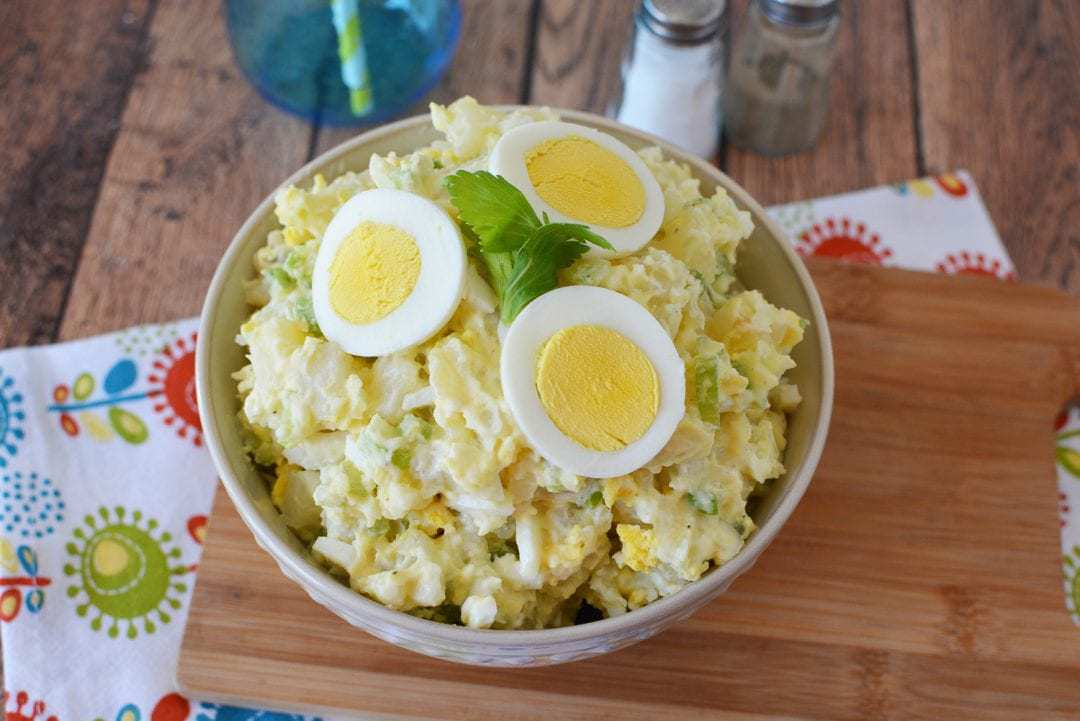 Potato Salad in a white bowl with three eggs on top
