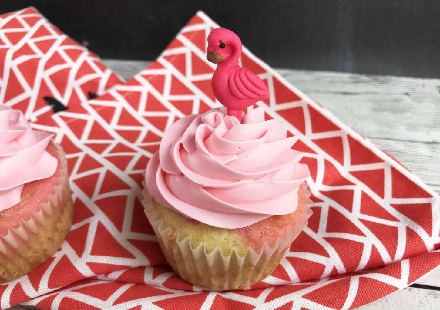 flamingo cupcakes with pink icing and a flamingo candy on top