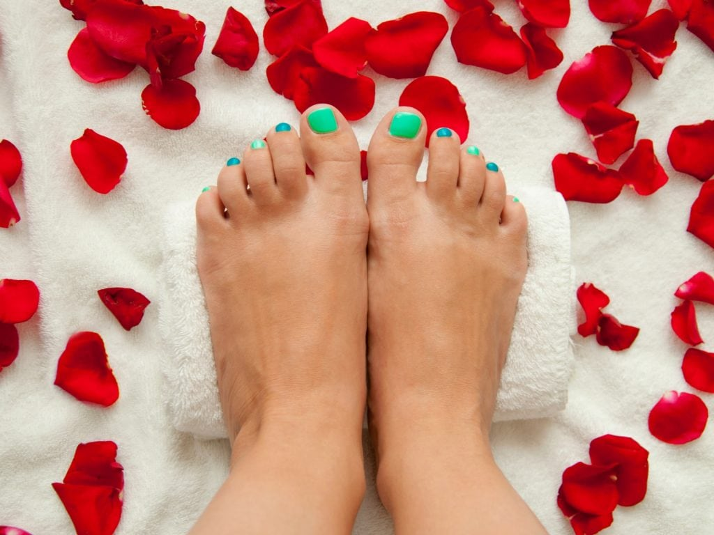 spa day, manicured toes, rose petals, green nail polish on toes