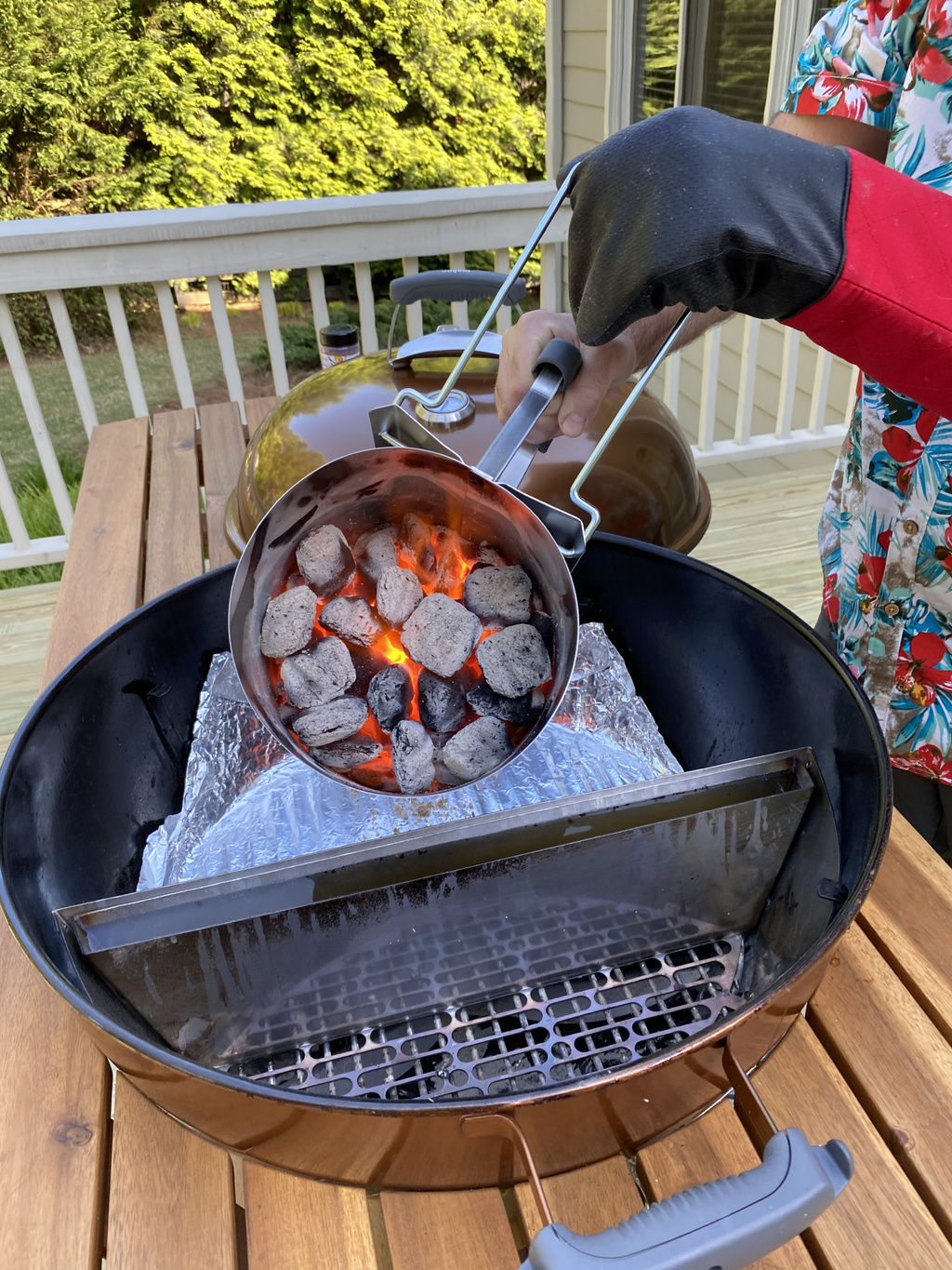 man pouring charcoal on grill
