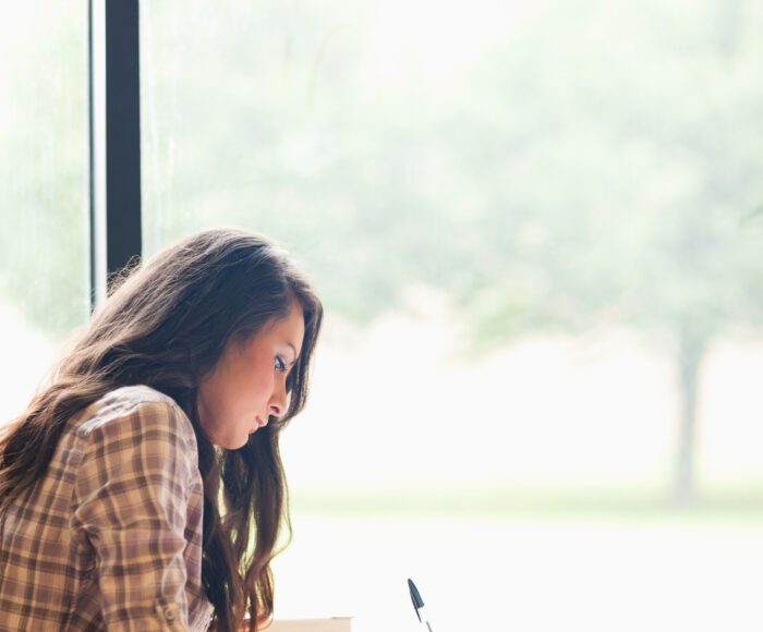 student writing an essay in a library