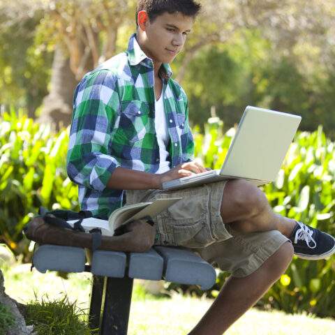 Teen student studying with backpack studying outside