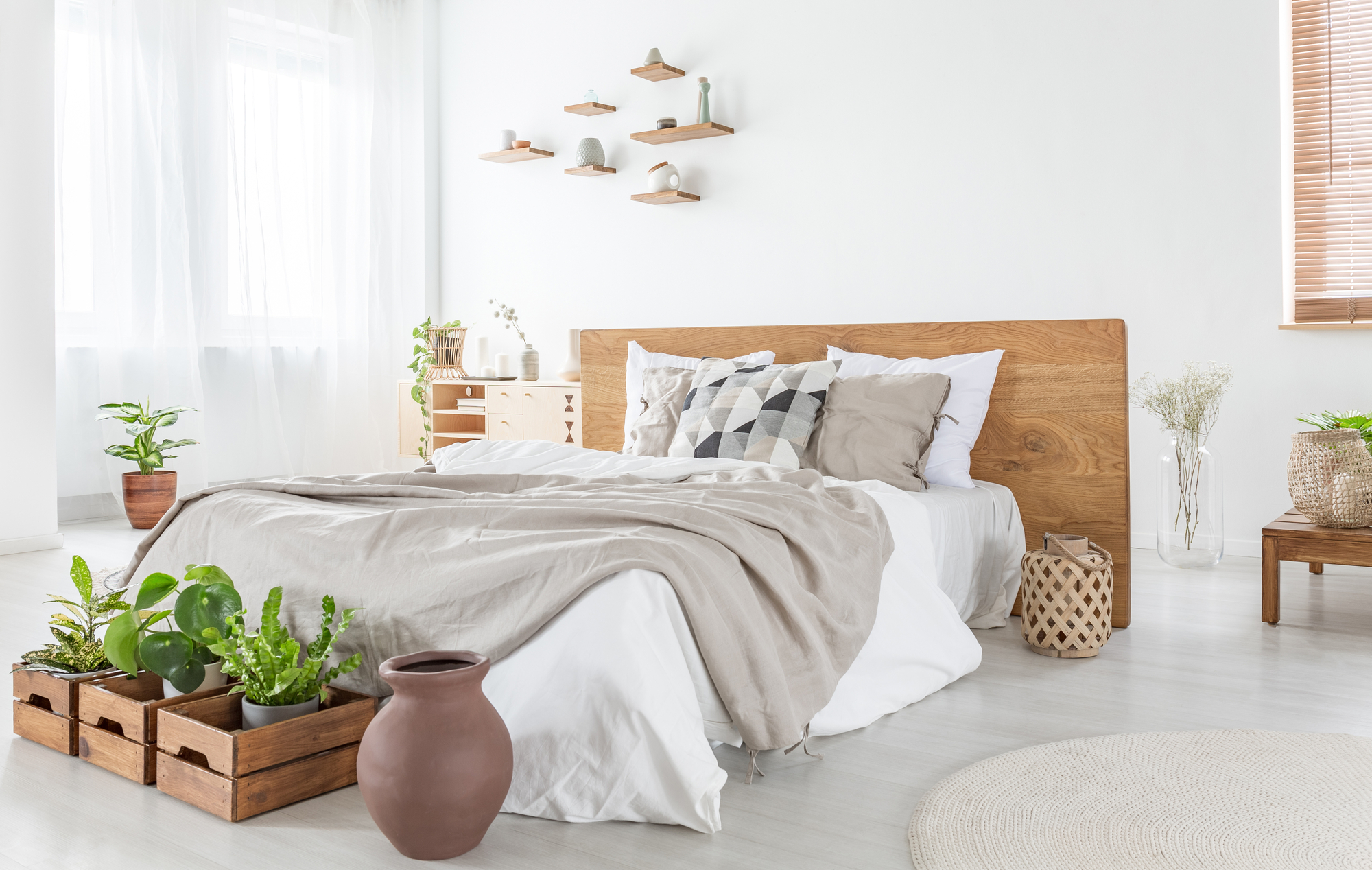Pillows and sheets on wooden bed in bright bedroom