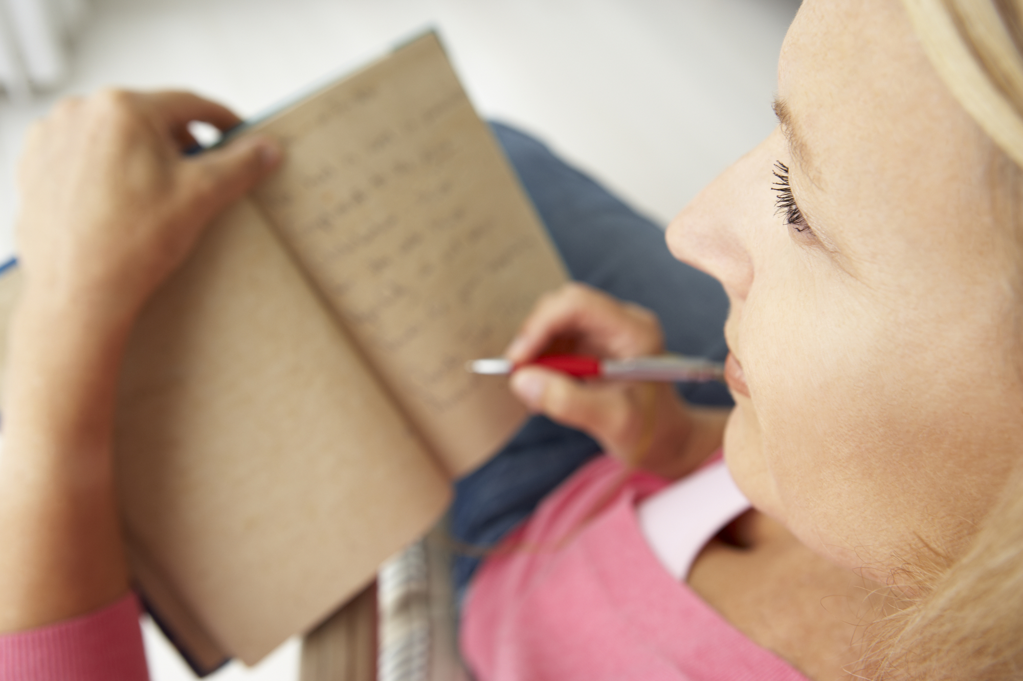 woman writing in notebook and taking time for herself